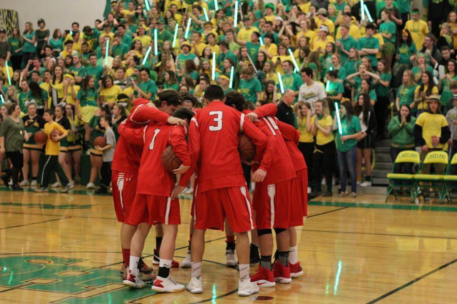 The basketball team huddles in preparation for the game.