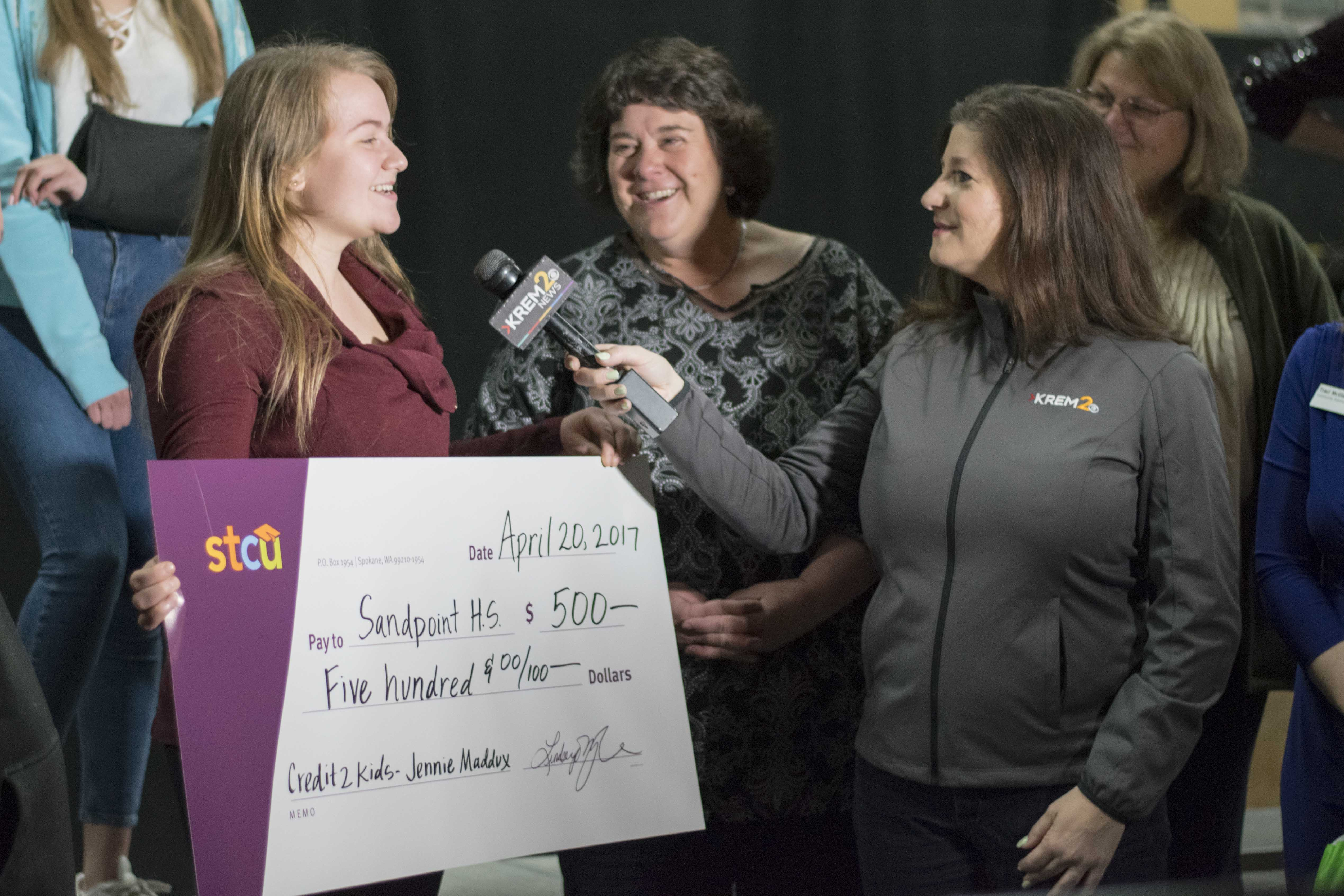 Junior Jennifer Maddux receives $500 from KREM 2 News and STCU while in her choir class. Maddux's parents and school counselors Jeralyn Mire and Cindy Albertson were with the news team to present the check.
