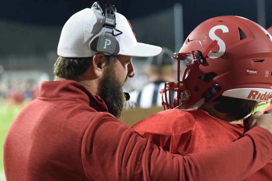 Coach George Yarno advises a football player on the sidelines during a game.