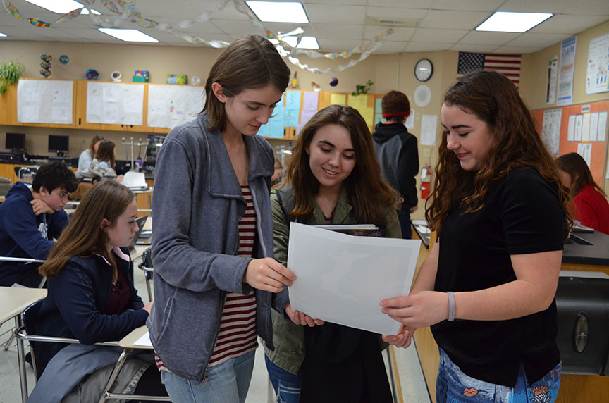 Left to right, Human Rights Club President Soncirey Mitchell, President-Elect Emma Dreier, and Vice-President Emma Reed study a poster advertising the Women's March.