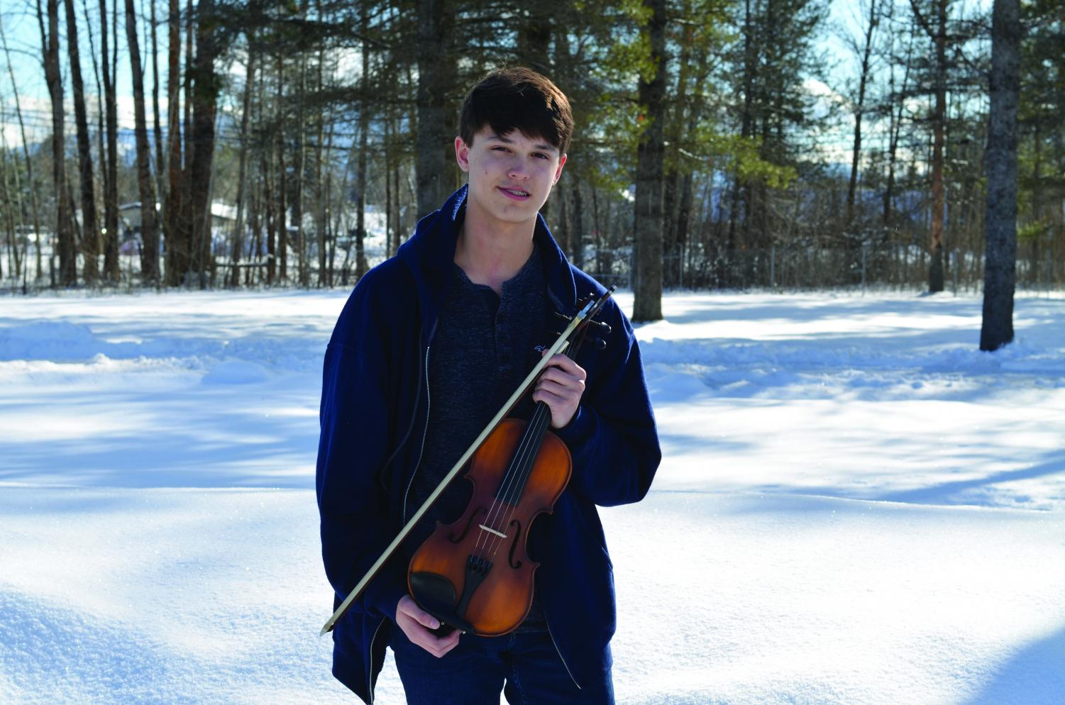 Max Reed poses along side his violin and bow.