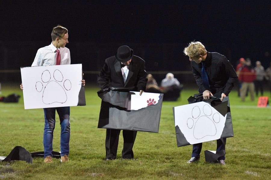 Seniors Curtis Hauck, Eliyah Allen, and Bruin Jones hold up their signs to find out the winner of Homecoming King.
