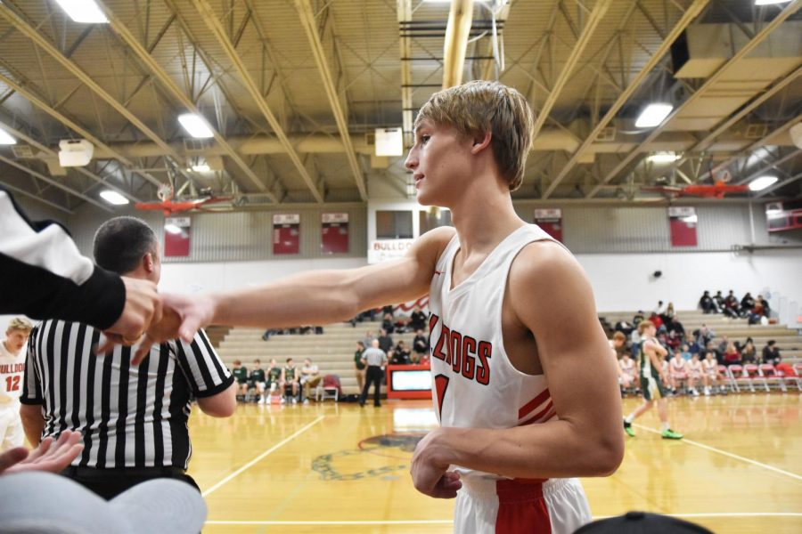 Junior Ryan Roos greets a fan member during a dead ball.