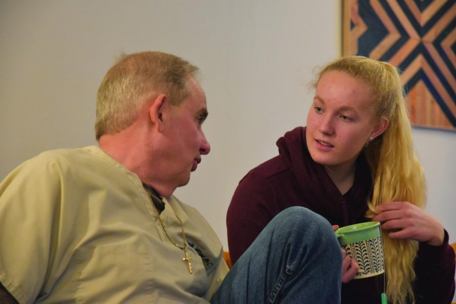Sophomore Hattie Larson speaks to a community member at the Fitchett home.