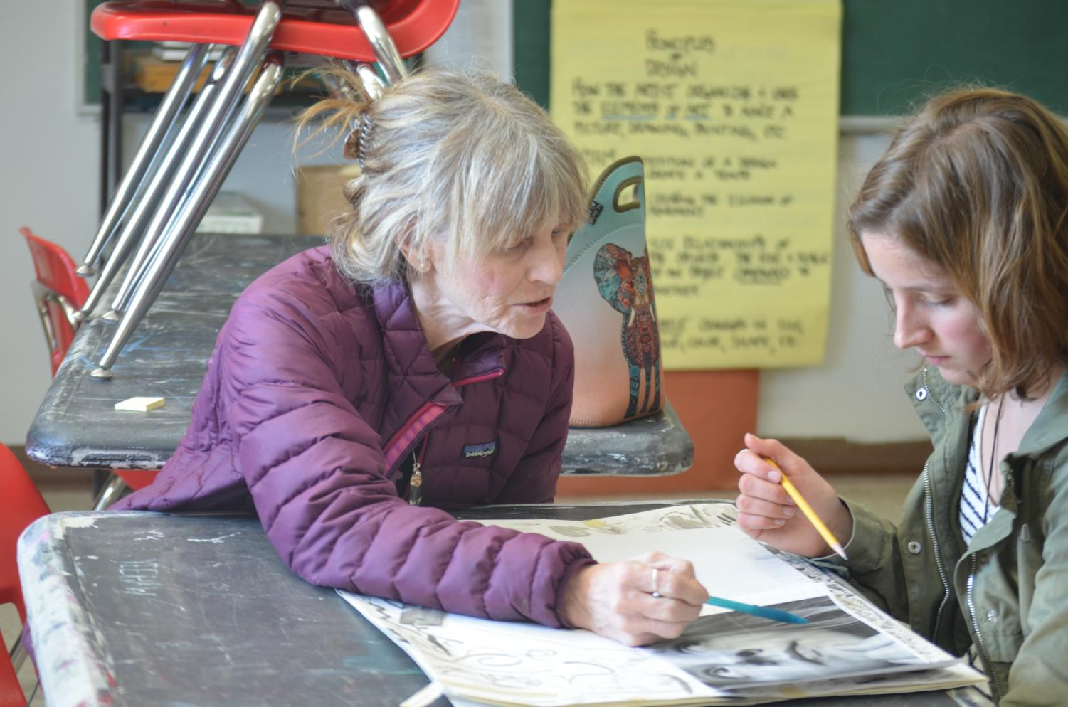 Guthrie gives one of her advanced students assistance on an art project.  Long time art teacher Heather Guthrie gives pointers to one of her advanced students, senior Chloe Braedt, as she works on a project for the class