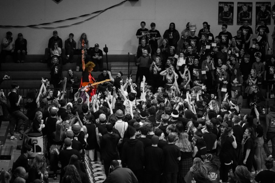Sophomore Kjetil Lund-Andersen plays the electric guitar as the Sandpoint student section storms the court at the annual Battle for the Paddle against Lakeland High School.