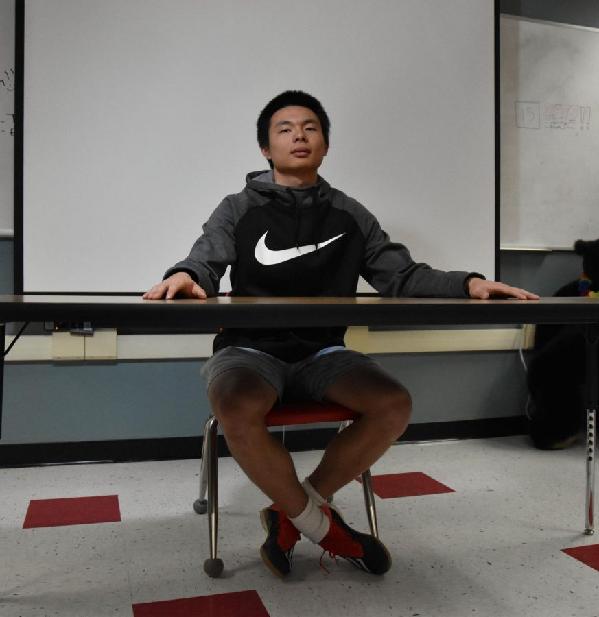 Zhong recreating the old photo in front of a classroom in Sandpoint High School.