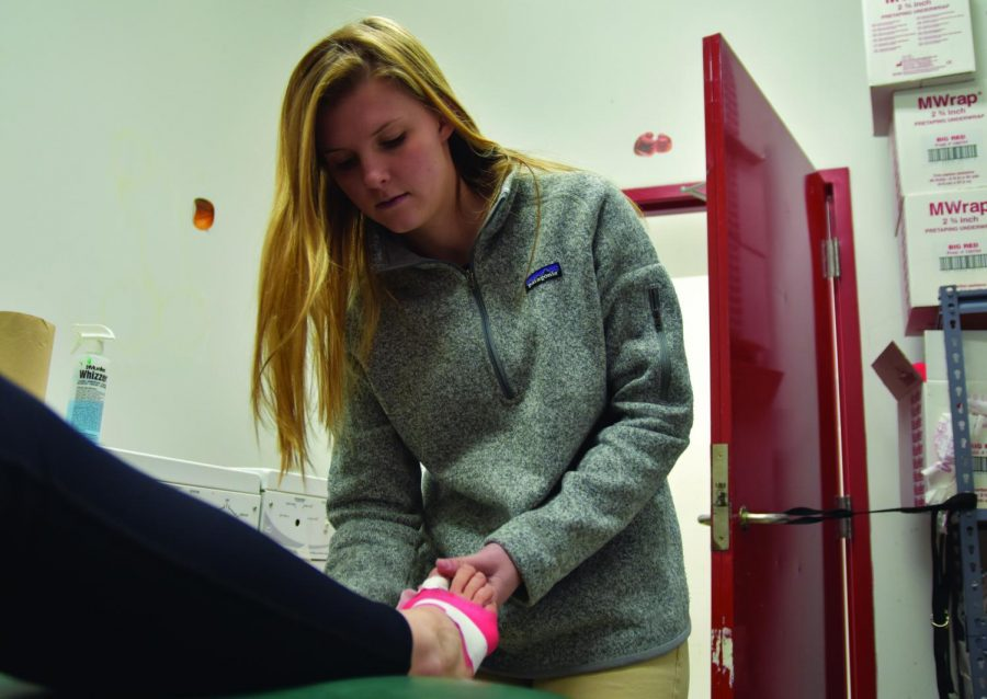 The new Athletic Trainer, Molly Radonich, helps Sandpoint High School athletes with their injuries in her office before practice, located inside the weight room.