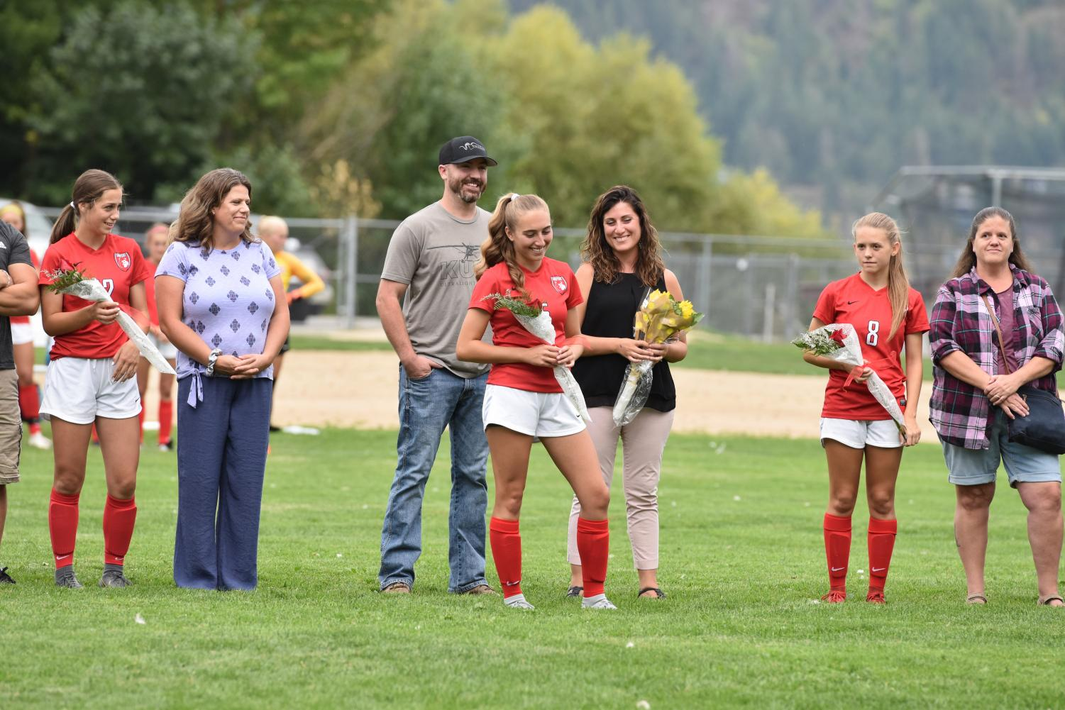Seniors+Kiley+Webster+%28left%29%2C+Shelby+Mohler+%28middle%29%2C+and+Hannah+Eddy+%28right%29+line+up+with+their+parents+to+be+recognized+before+the+game+on+Senior+Night.+