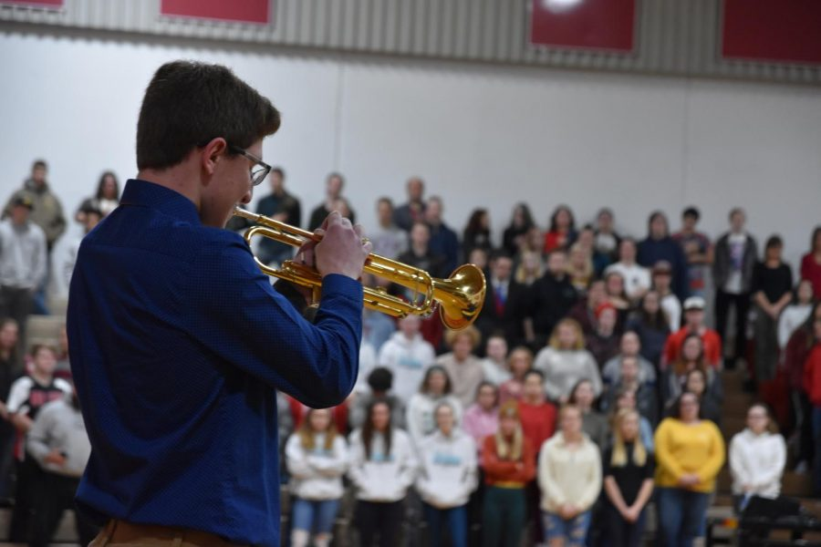 "Senior Nate Couch plays ""Taps"" in front of an attentive crowd."