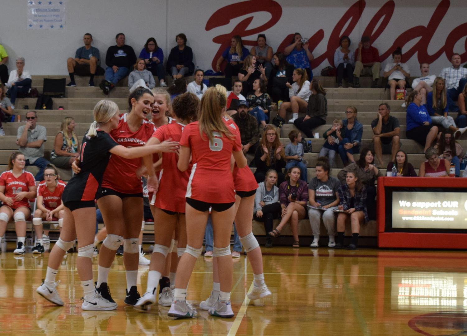 Varsity volleyball team celebrates a scored point against Lake City earlier this season.