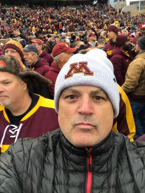 History teacher Kent Leiss takes a picture with the University of Minnesota crowd.