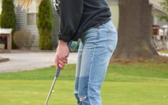 Junior Annaby Kanning attempts to putt the ball into the hole.