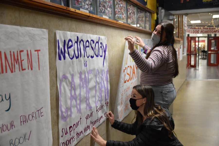 Members of student council hang handmade posters that say what each dress up day during spirit week is.