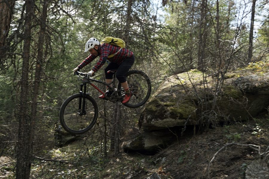 Ezra Stafford drops off a rock while braving a mountain biking trail.